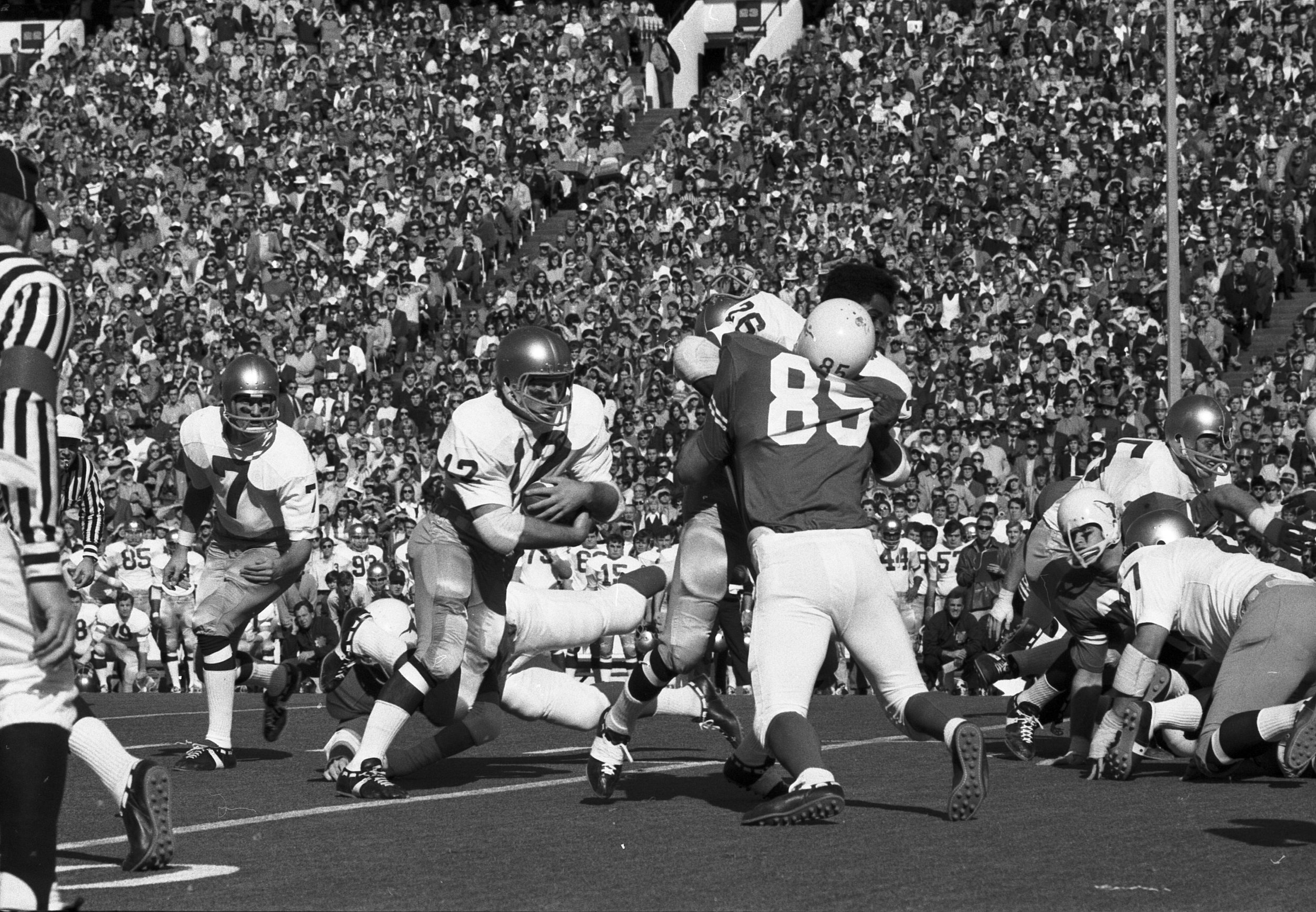 Stan Mauldin #85 knocks the helmet off the Notre Dame blocker. Joe Theisman is #7. Notre Dame Coach Ara Parseghian is squatting down on the Notre Dame sideline by number 44.