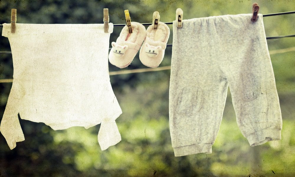 Baby clothes hanging to infer a woman is currently on maternity leave and needs legal assistance