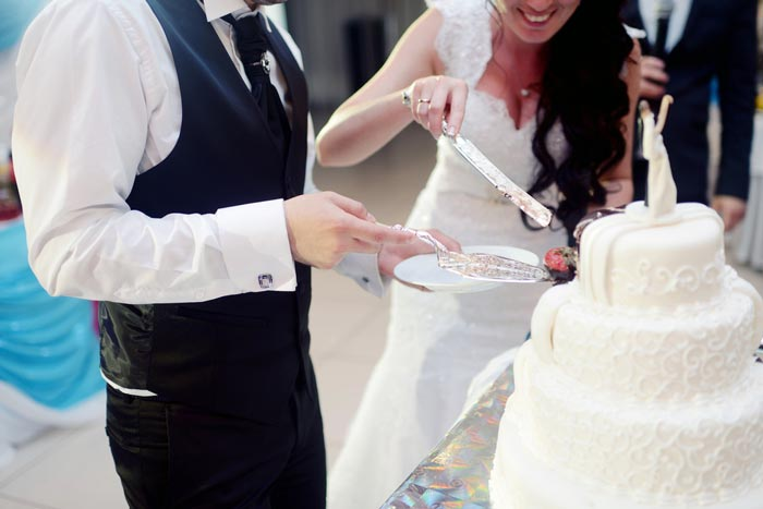 Two newly weds cutting a wedding cake