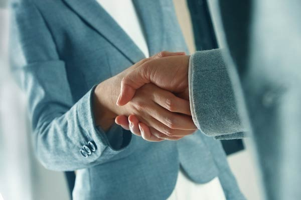 Two lawyers shaking hands over legal agreements