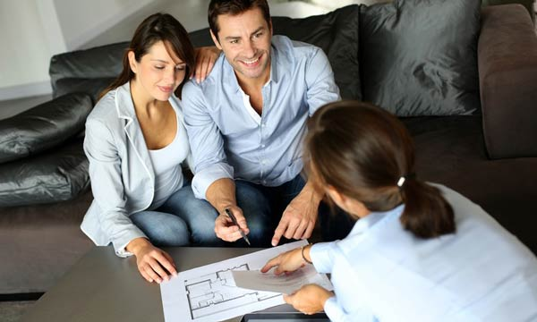 A pair of first time buyers going over planning permission with lawyer
