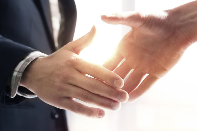Two businessmen shaking hands over a legal agreement