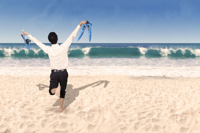 Man wearing suit on beach, indicating a worker on annual leave