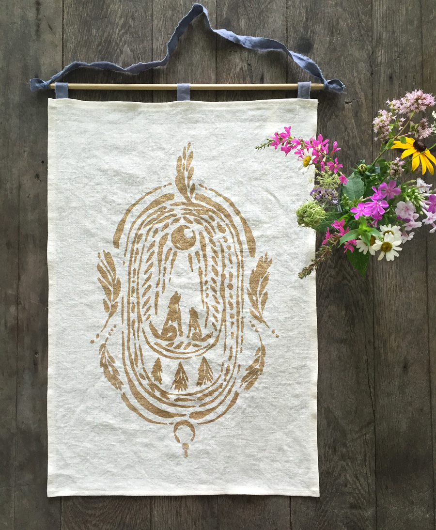 Wild Altar banner with mama wolf & pup, feathers, and evergreen trees