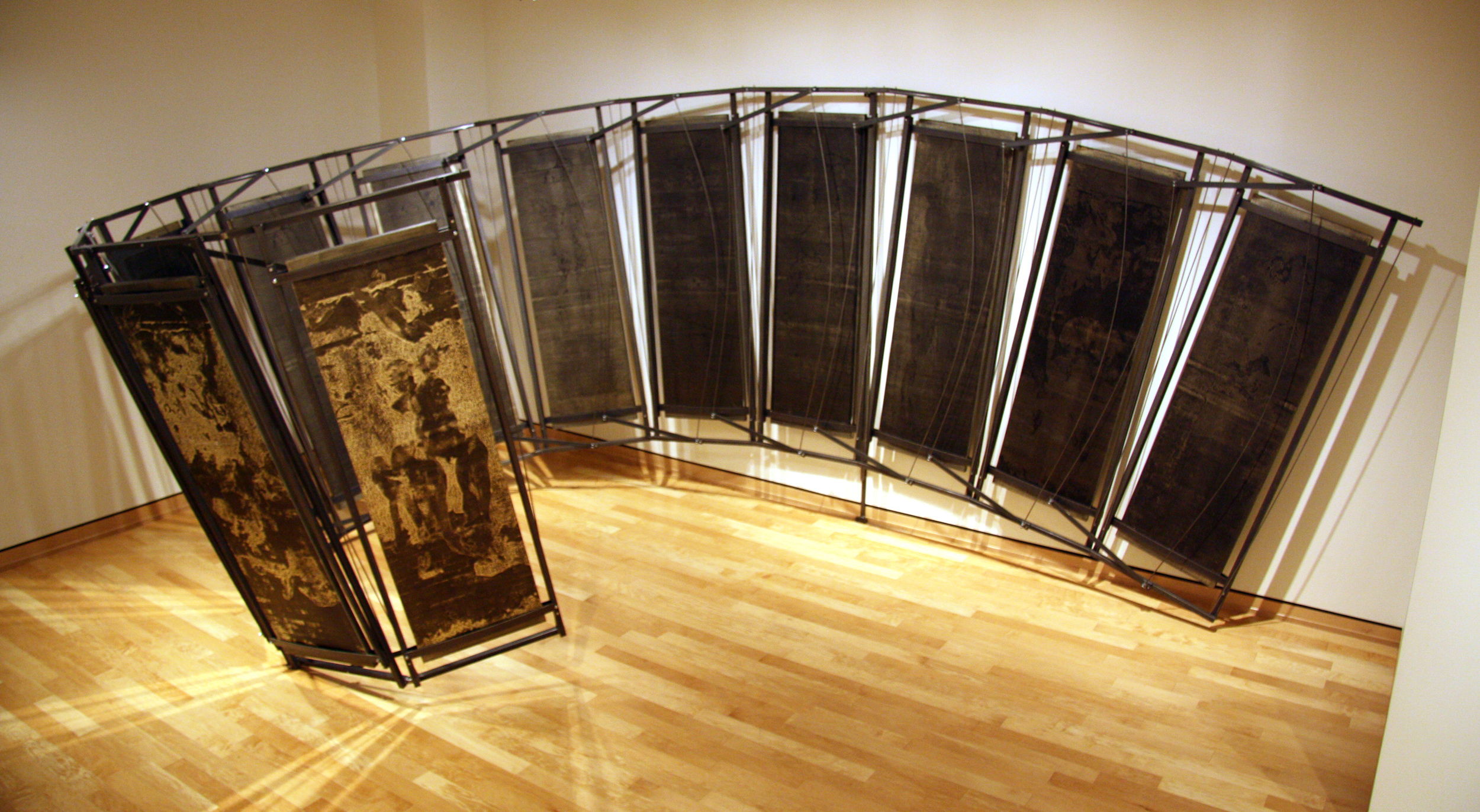 """Radius    twenty-four monoprints, mounted on twelve wooden panels, assembled in twelve connected steel structures monoprints; ink, paper and metallic foil.   sculpture; wood and stee 22' x 15' x 9.5'   (264"""" x 180"""" x 114"""" 2013  The steel and wooden panels of Hager's installation appear to reach out to encircle the viewer, offering an alternative space at odds with the larger room.   Pitched off-kilter, the regimented shapes ordered by industrial materials and taut cables offer yet another contrast.   On each dark panel, the soft glint of metallic foil makes visible organic shapes, reminiscent of an emerging human figure.   The stability that we expect of steel construction is undermined not only by the precarious angle but also by the faint figures that compete for the viewer's attention.   Despite our predisposition to trust structures that resemble engineered works, we approach this large work with caution, preoccupied with the struggle of the forms against the framework, the framework against the wall.  Dr. Kelly Watt, Assistant Professor of Art History Washburn University"""