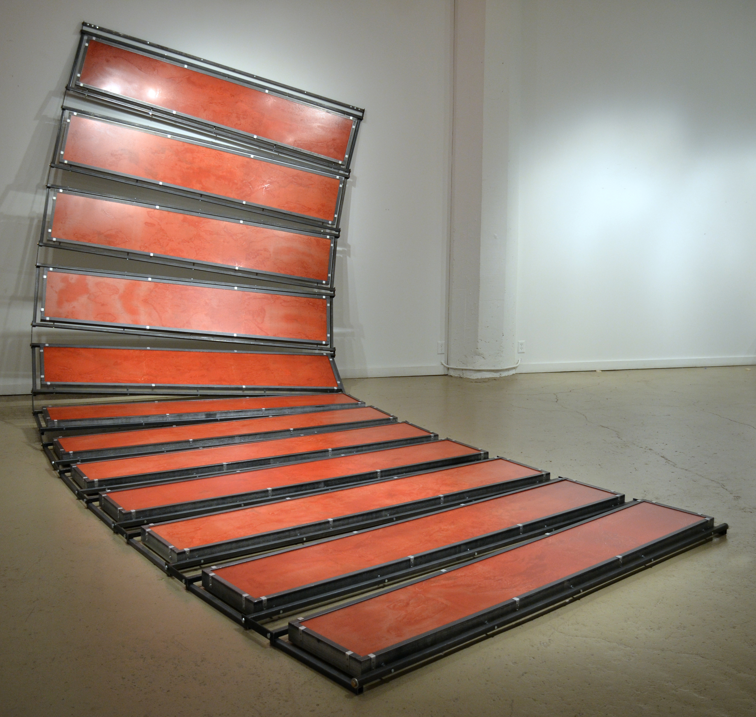 """Flow    woodcut printed on plastic sheets, mounted on 12 prepared boxes with maps, affixed into steel structures, mounted on a wall as to cascade onto the floor. plastic, ink, maps, wood, steel 120"""" x 180"""" x 120"""" (10' x 15' x 10')   2012   Flow  is a transitional piece for me.   I am beginning to use the physical structure of the work as an aesthetic element.   How the sculpture is put together and the function of each of the varied materials used is plane to see (This also can be said about  Basin ).   I enjoy letting the viewer explore the creative history of this sculpture."""