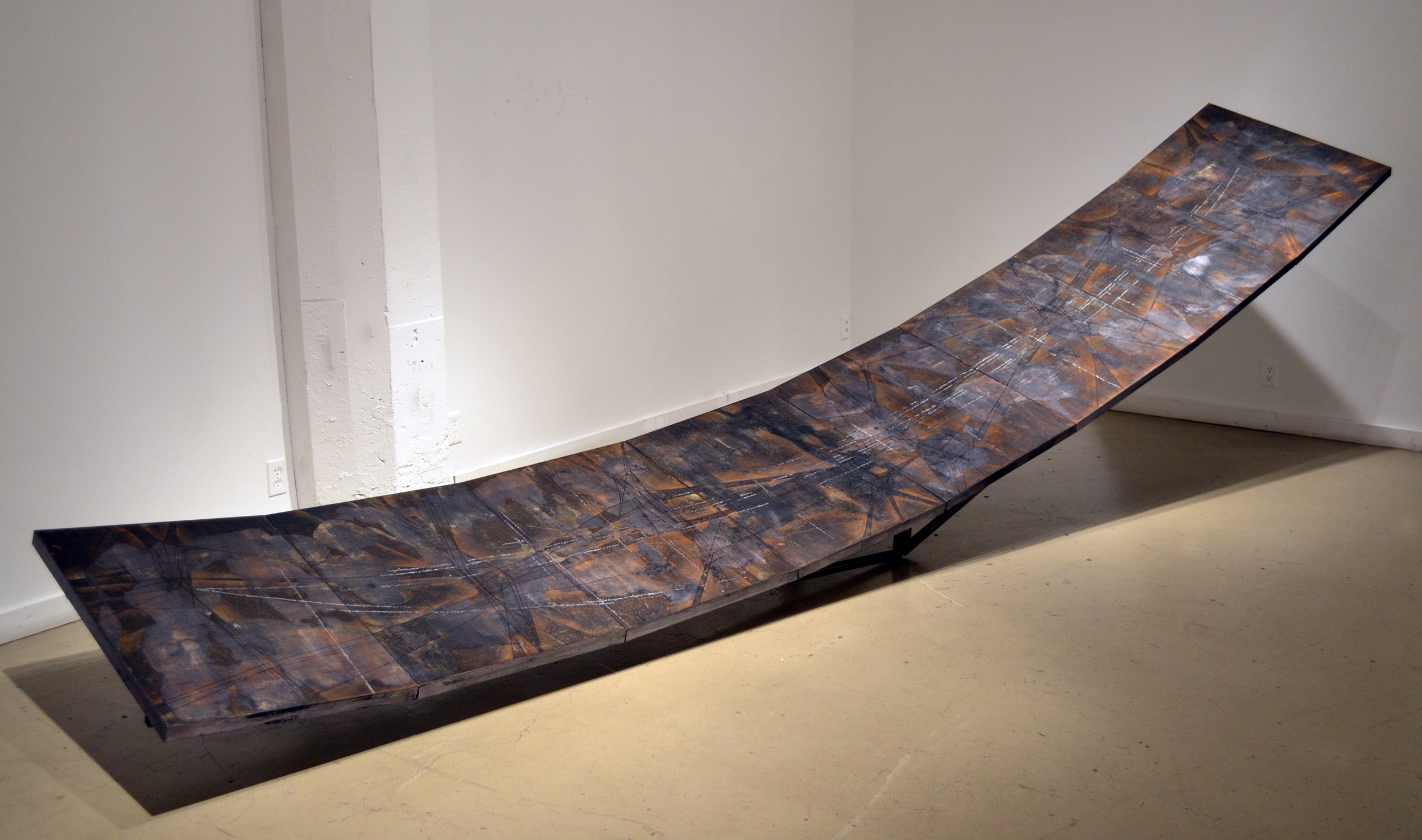 """Balance    woodcut monoprints with metallic foil, mounted on prepared panels, arranged on an inverted arc structure. paper, ink, metallic foil, wood, steel 192"""" x 32"""" x 48""""   (16' x 2'6"""" x 4')   2012  The making of  Balance  presented me with a fundamental question.   At what point does the supportive sculptural structure become just a means to display my prints?   I dealt with this conundrum for over a year with this work.   I felt that the printed images did not go well with the inverted arc, making me question my approach with combining prints with sculptures.   Ultimately, geometry came to the rescue with the addition of the strong graphic drawings on the prints."""