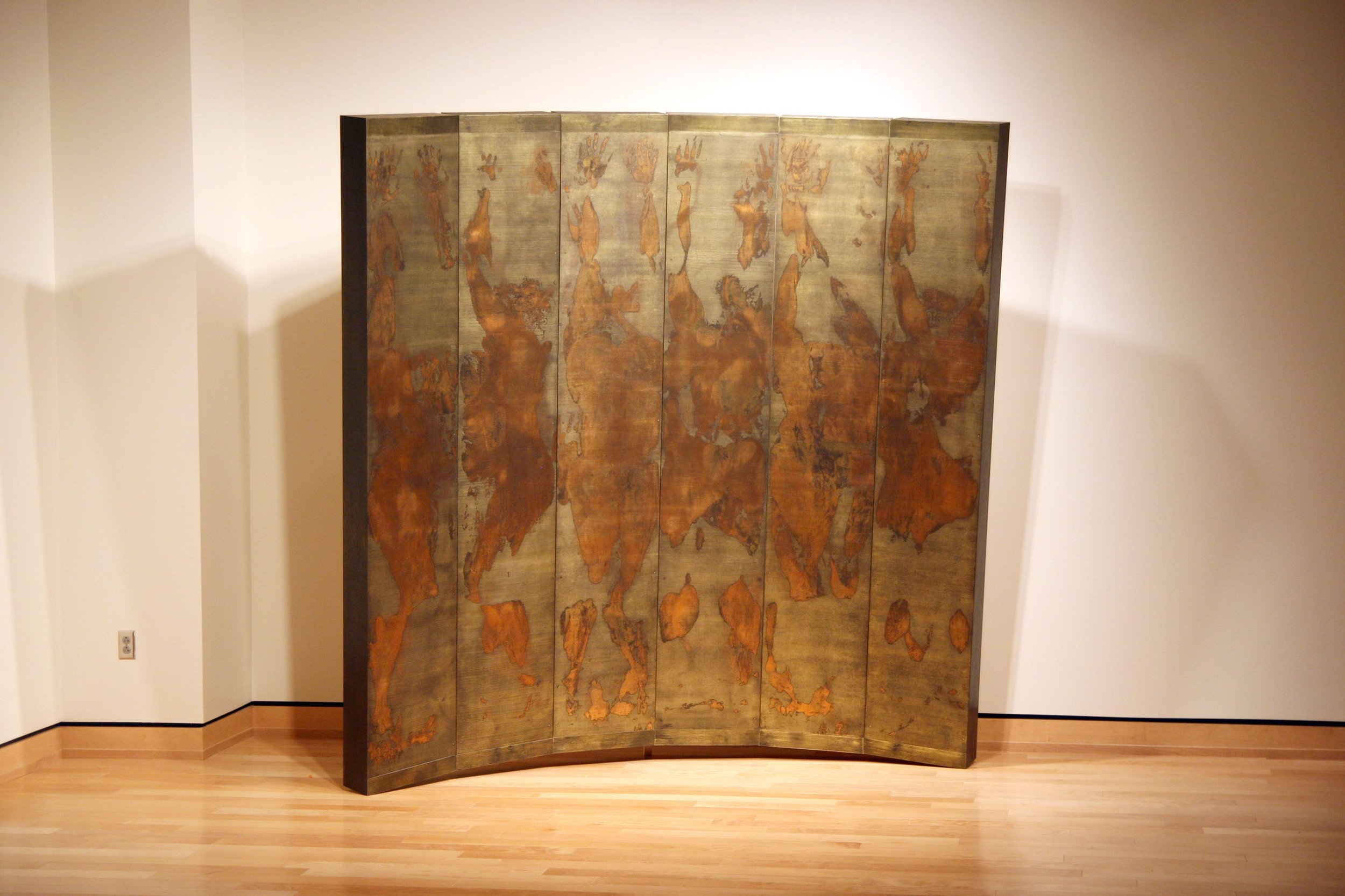 """Pusher     woodcut monoprints, mounted on prepared boxes, assembled in a tilted horizontal arc form paper, ink, metallic foil, wood, oil paints, hardware 96"""" x 96"""" x 24"""" 2010"""