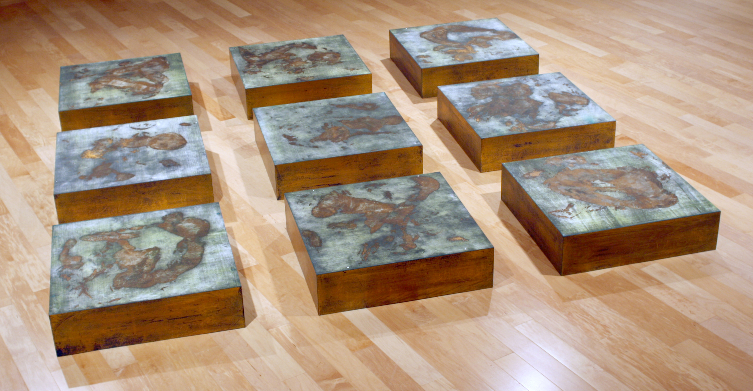 """Foundation   woodcut printed images on paper, mounted on constructed boxes, to be installed in a 3 x 3 grid arrangement with approximately 12""""spacing. ink, paper, metallic foil, wood 29"""" x 29"""" x 7 ½""""   (each unit) 110"""" x 110"""" x 7 ½""""   (9 units installed) 2008   A Statement on  Foundation     Nine identical square wooden boxes are laid out in a precise three by three square on the gallery floor.   Such systematic ordering of forms might reference minimalism, were it not for the fact that the surface of each box exudes the earth-mellow glow of copper and the bluish-green of malachite, copper's mate in earth's geology.   The severe geometry of the squares-within-squares is tempered, if not contradicted, by the randomness of the malachite-hued shapes that seem to float like islands on a copper sea.   The entire work is a play with complementarities of opposites and their transcendence: geometric regularity – culture in classical tradition – verses organic line – nature; copper's warm color and malachite's cool hue; land and water, male and female; the corporeal bulk of the boxes and the lyrically light markings of the paper prints which they support.   Hager obtained the accidental shapes by literally rolling male as well as female nude models smeared with paint inside a large wooden box, and the side of the box that carried the body's imprint then became the matrix for the two-color woodcut.   The grain of the wood remains visible and becomes part of the traces left by human presence.   Earth-bound, yet luminous with spirit as light reflections in the metallic colors animate – literally """"giving soul to"""" – the forms.   The sculptor and printmaker Hager has gracefully married his media by taking the print off the wall.   Reinhild Kauenhoven Janzen , Professor of Art History, Washburn University Art Department 2008"""
