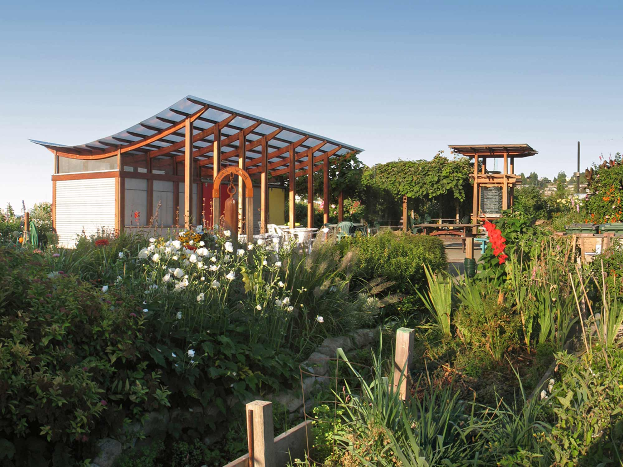 A simple structure that creates a plaza in the middle of the garden, provides shelter for community functions, tool storage, and gathers rainwater for reuse.