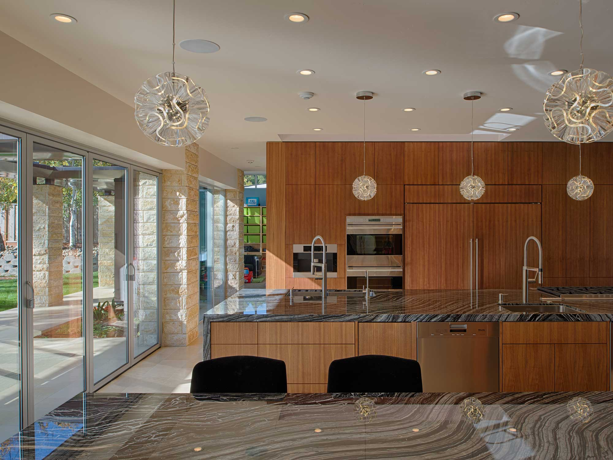The house is build for entertaining, with a dramatic 14' x 5' kitchen island packed with function and ample storage is hidden away in full height walnut cabinetry.