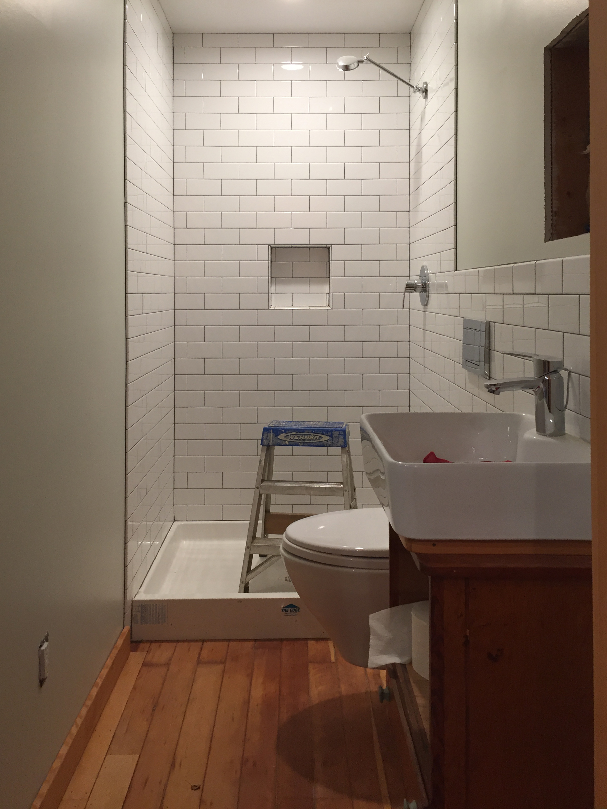 A new bathroom on the main floor finds a snug but workable home in what used to be a hallway.