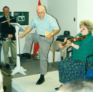 Amand Arsenault kick up his heels while Zélie-Anne fiddles and Georges Arsenault looks on.