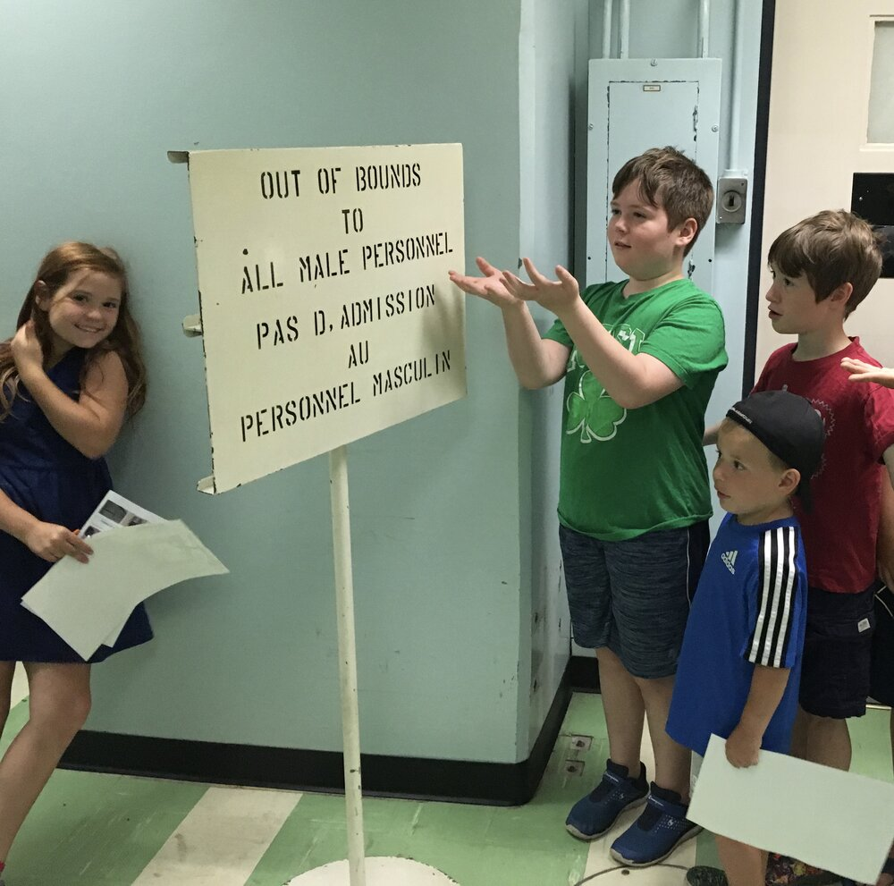 "kids at the diefenbunker by a sign that says ""out of bounds to all male personnel"""