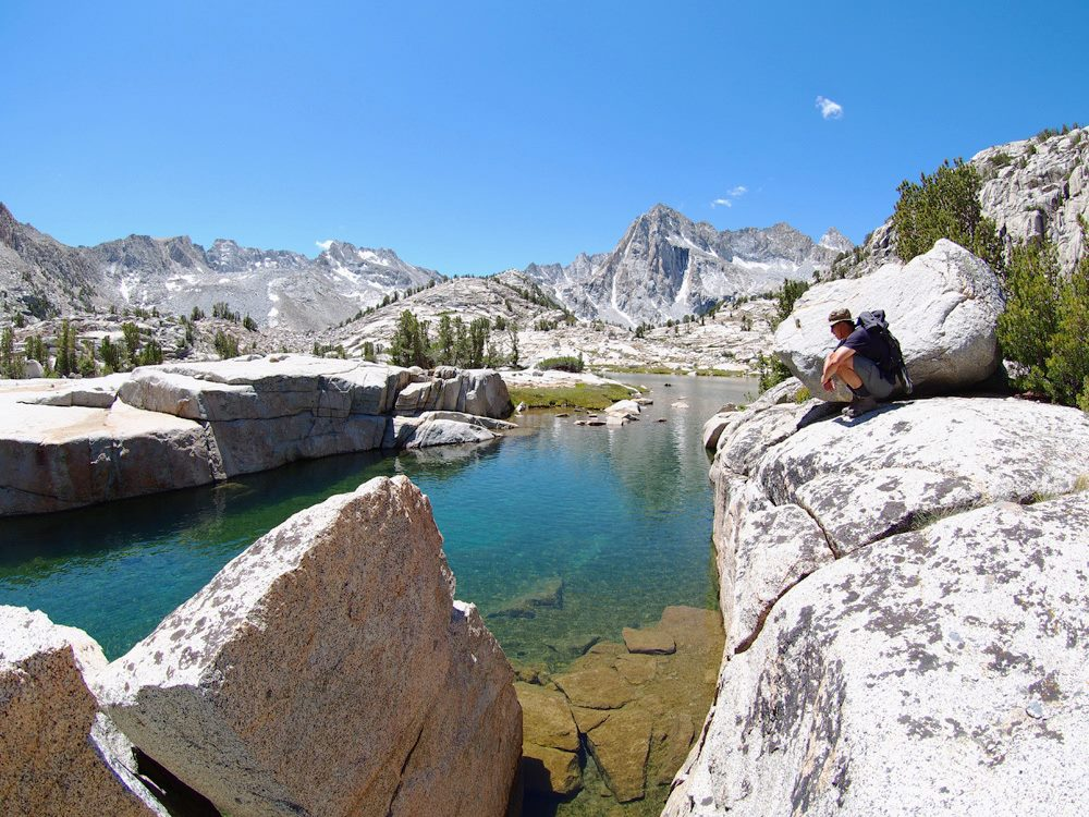 Ed sitting above the crystal clear waters of Hungry Packer lake