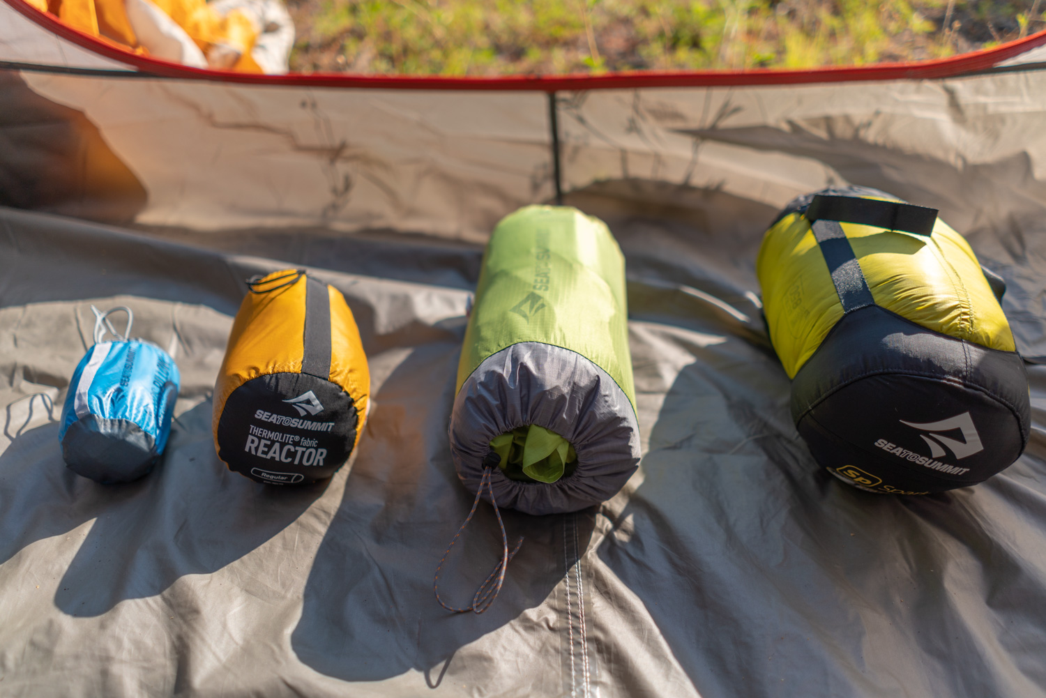 A range of Sea to Summit's gear for size comparisons from left to right:  Aeros Premium Pillow ,  Reactor Liner ,  Comfort Light Insulated Mat ,  Spark III sleeping bag