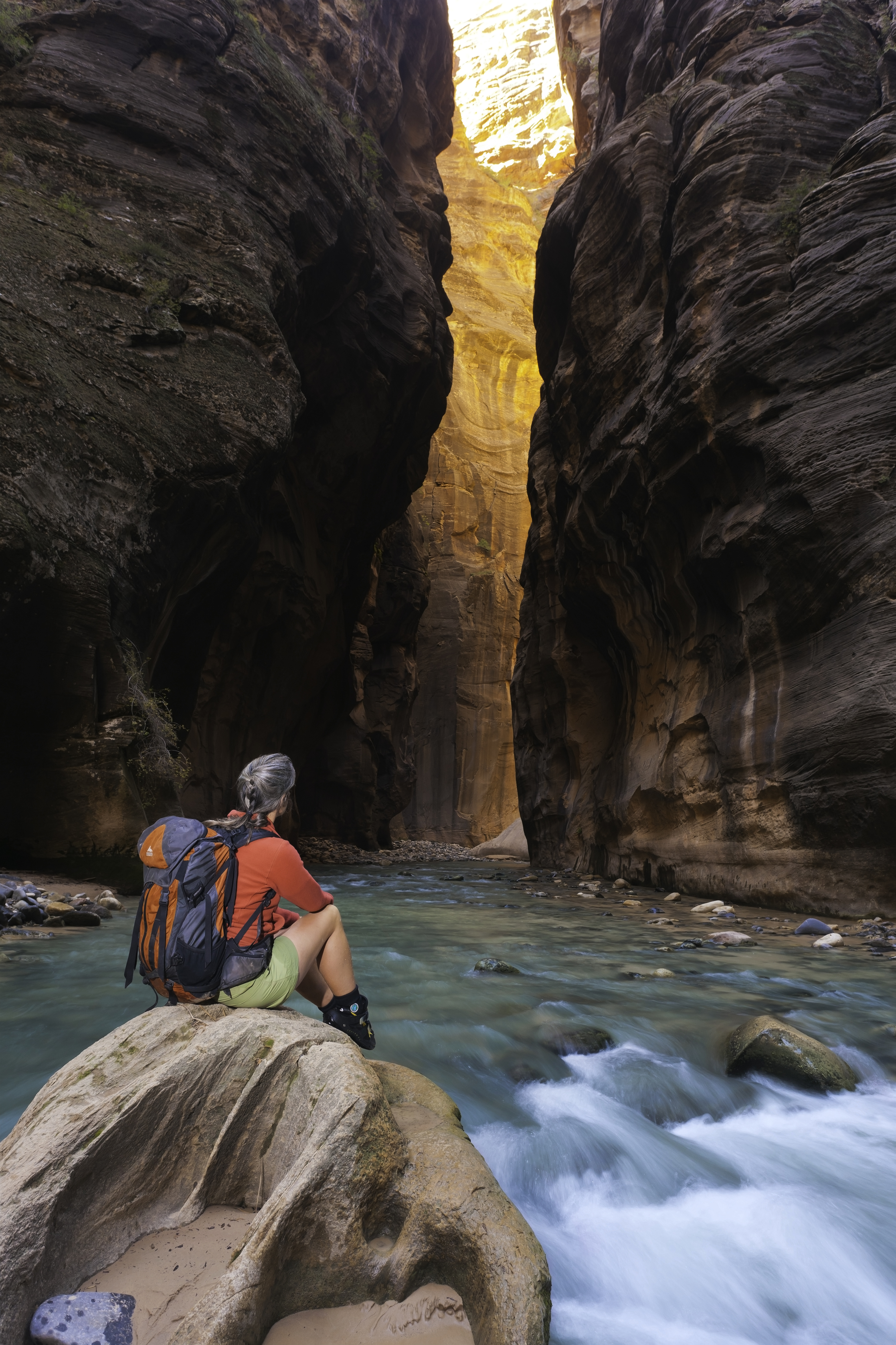 A hiker contemplates the beauty of the Zion Narrows.