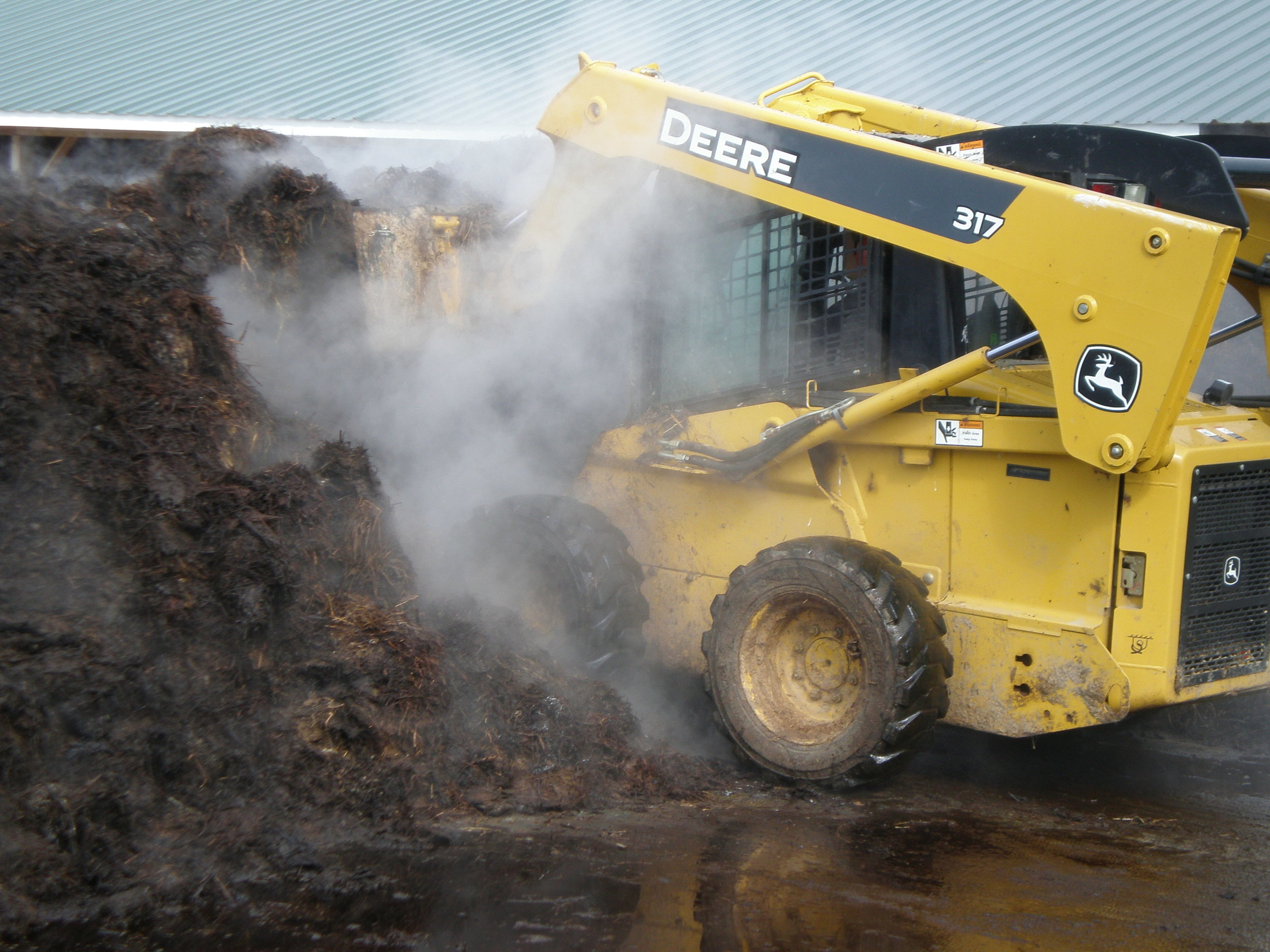 manure is turned between once and three times daily, depending on the stage of the compost process. the heat from the decomposing bedded pack creates enough steam to obscure the skid steer.