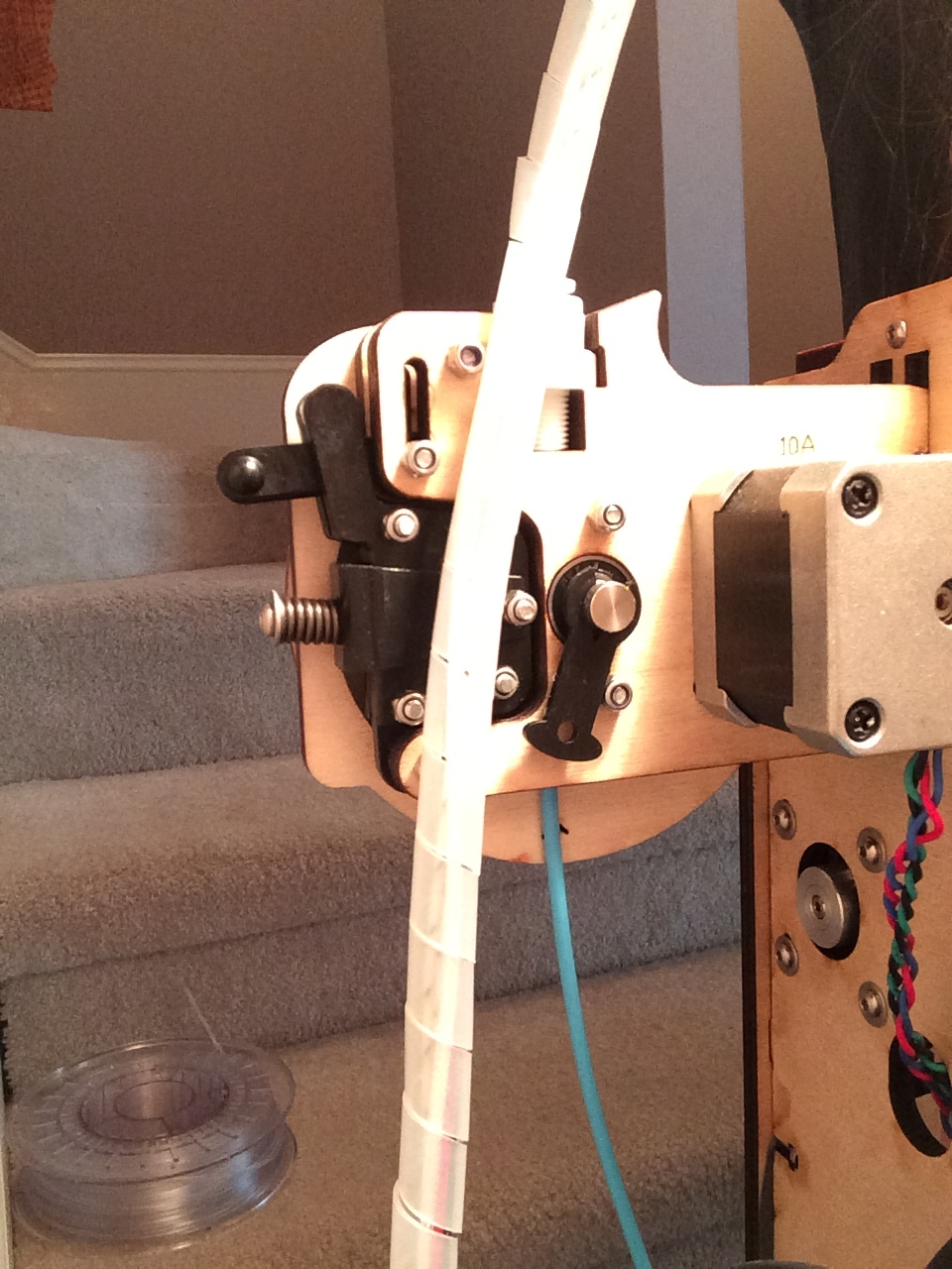 The material feeder mounted to the back of the printer with blue PLA plastic feeding through.