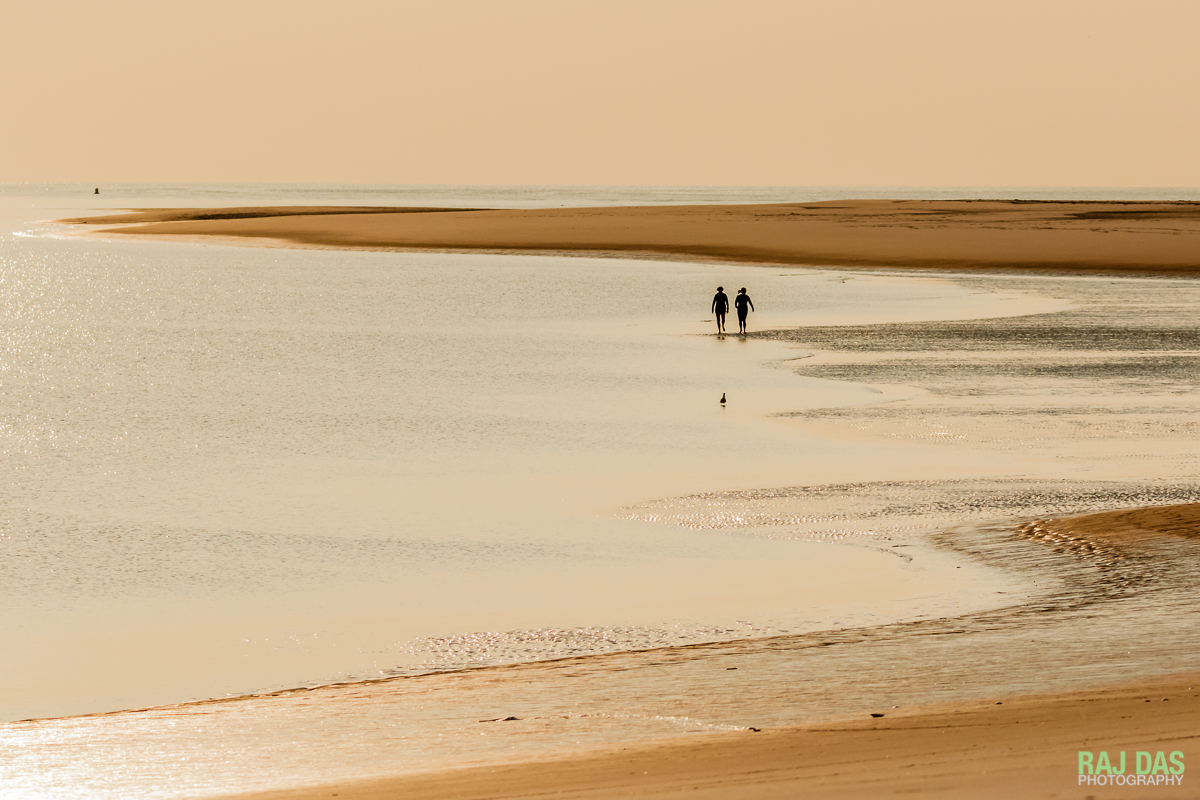 A pair of early morning walkers on the beach