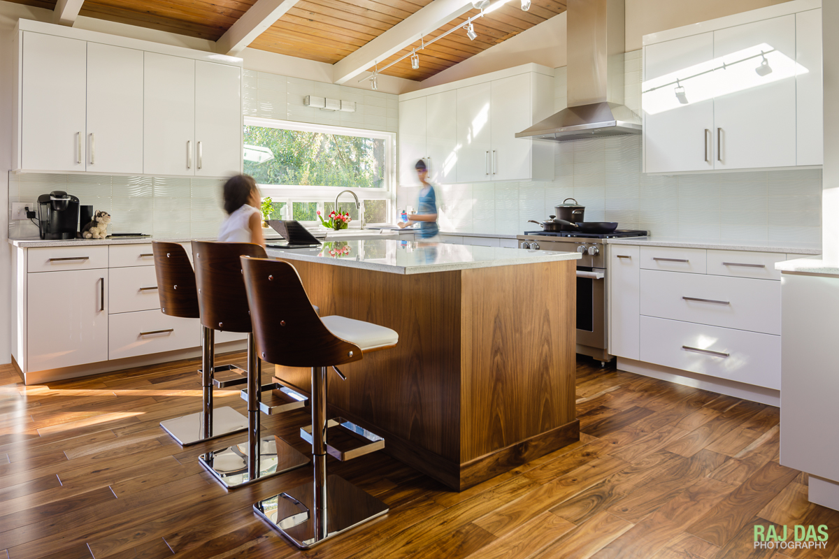 The whites of the cabinets and counter tops go very well with the brown and wood tones of the floor and ceiling in the newly renovated kitchen.