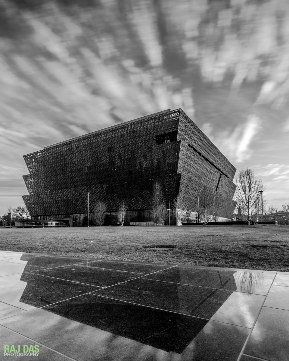 The Museum and clouds reflected on the black granite retaining wall along Constitution Avenue