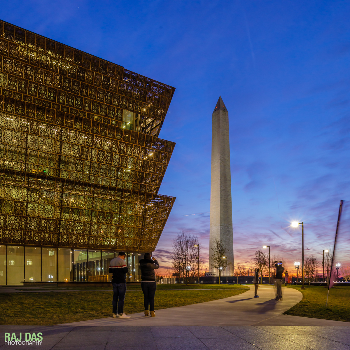 Visitors taking in the view of the Washington Monument from the Museum at dusk