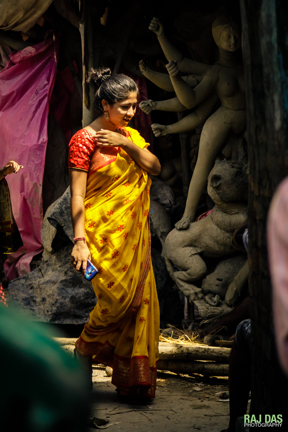 A young Bengali girl in a traditional sari walks past a Durga idol that is still being built