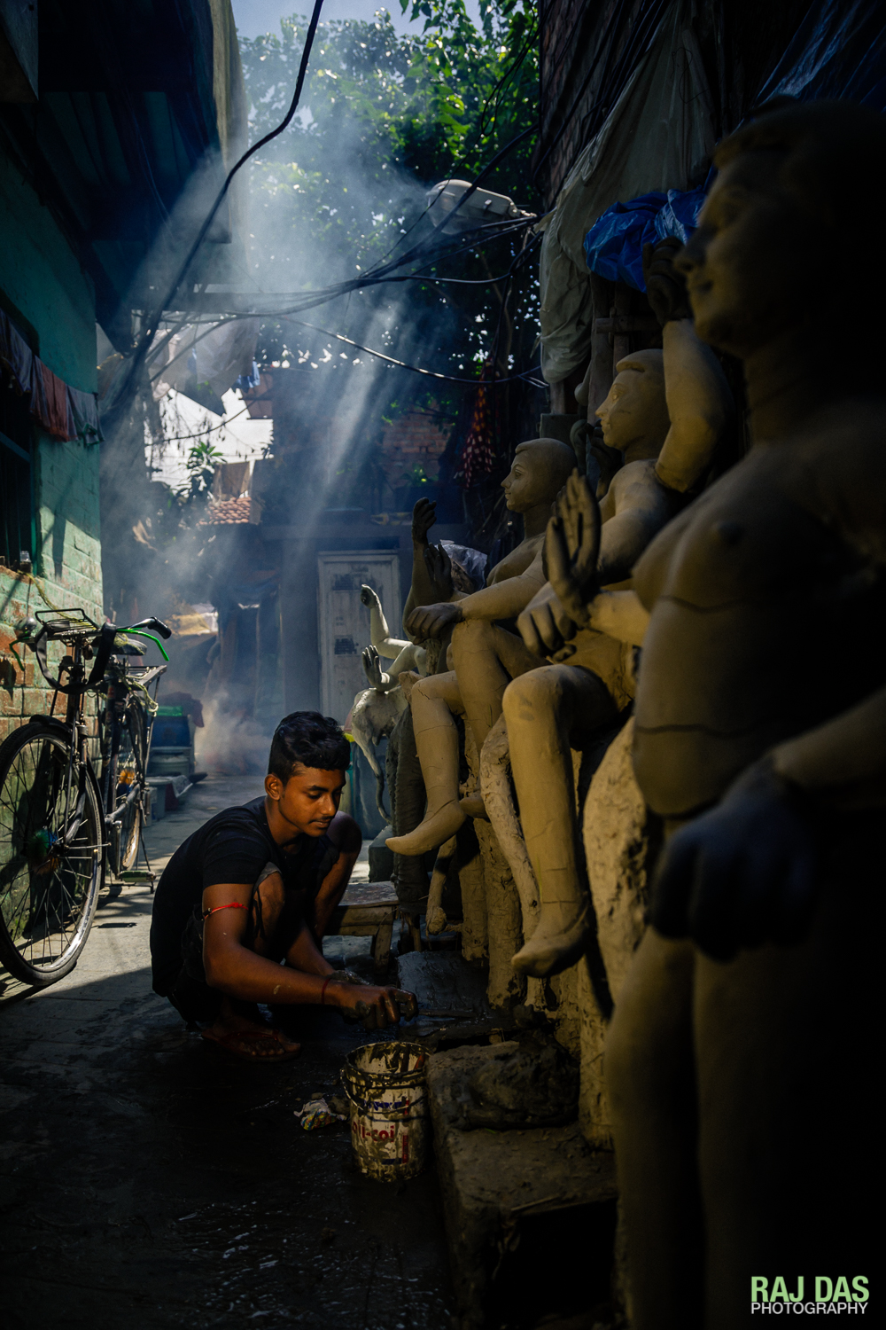 A young artisan applies a fresh coat to prevent the clay idols from cracking as they dry