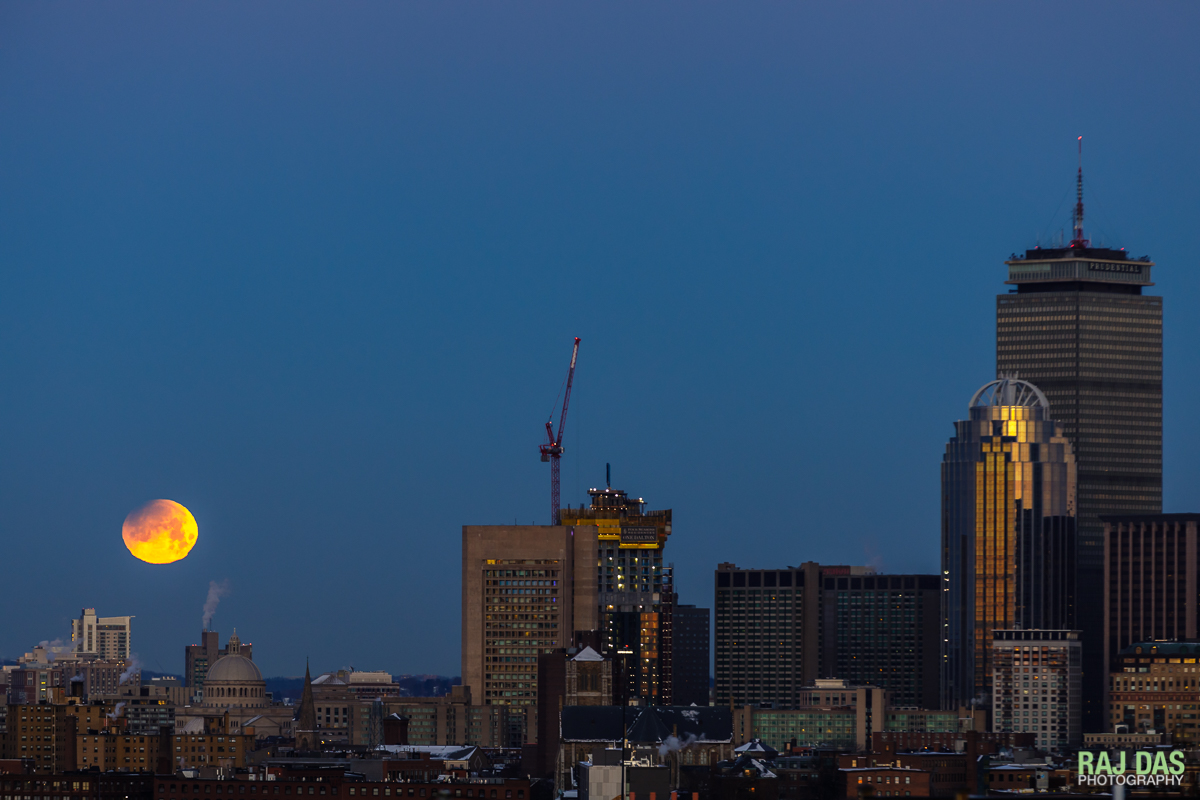 A super blue blood moon sets as the rising sun casts a warm glow over the Boston skyline with the Prudential tower visible on the right.