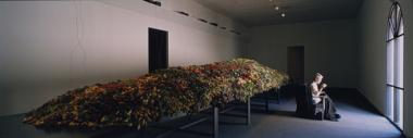 mantle, 1998, Miami Art Museum; a figure, hand-sewing wool coats, sits in front of a long steel table where multiple speakers connected to seven short wave radios are buried in a bed of fresh-cut flowers; photo courtesy Thibault Jeanson