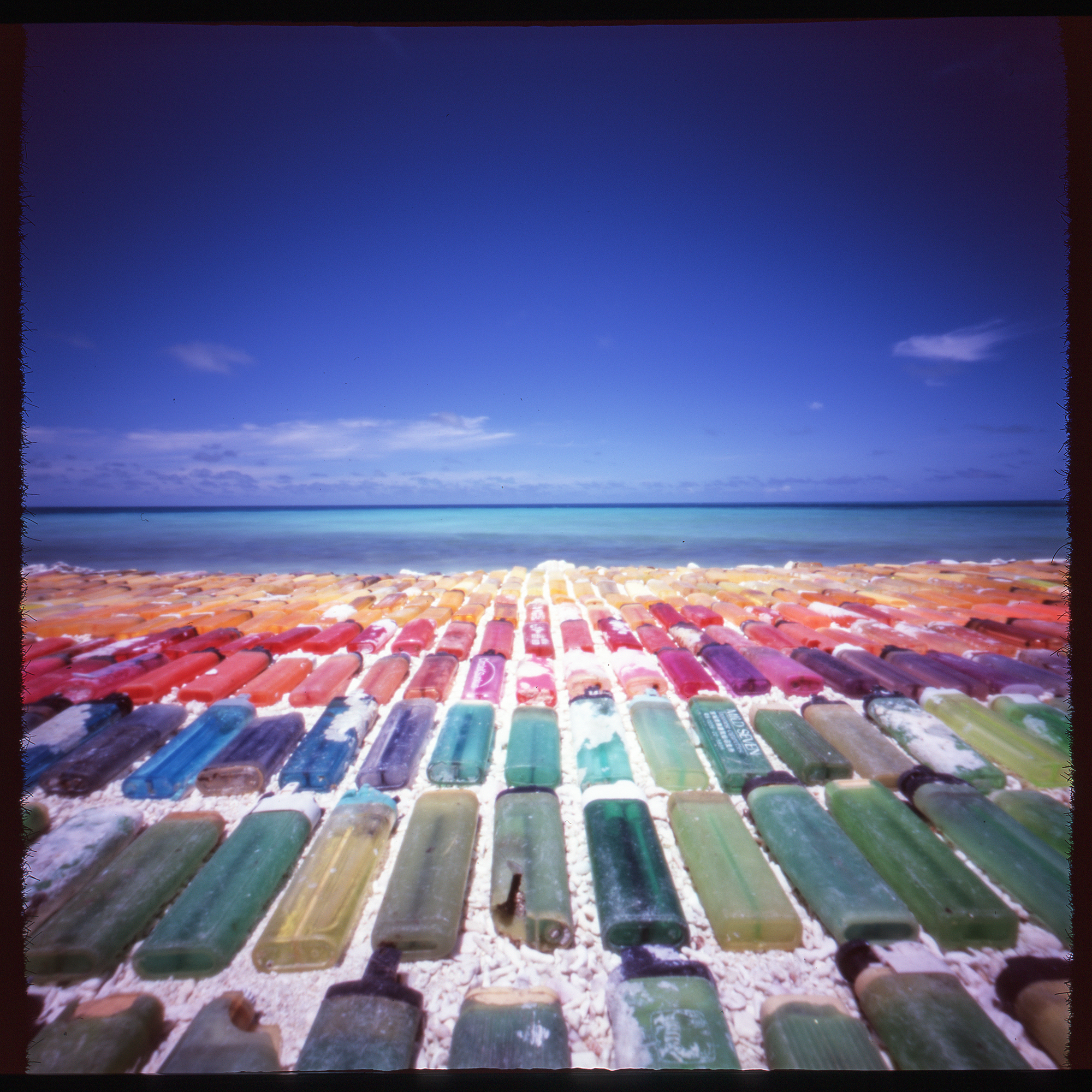 """""""Every Color Of The Rainbow"""" Onsite marine debris installation  of  found 'disposable'  lighters. Pinhole photograph, 2016."""