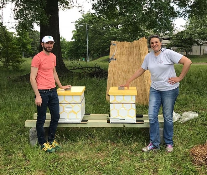The DC Beekeepers Alliance stands in front of their new hives at Wangari Garden.