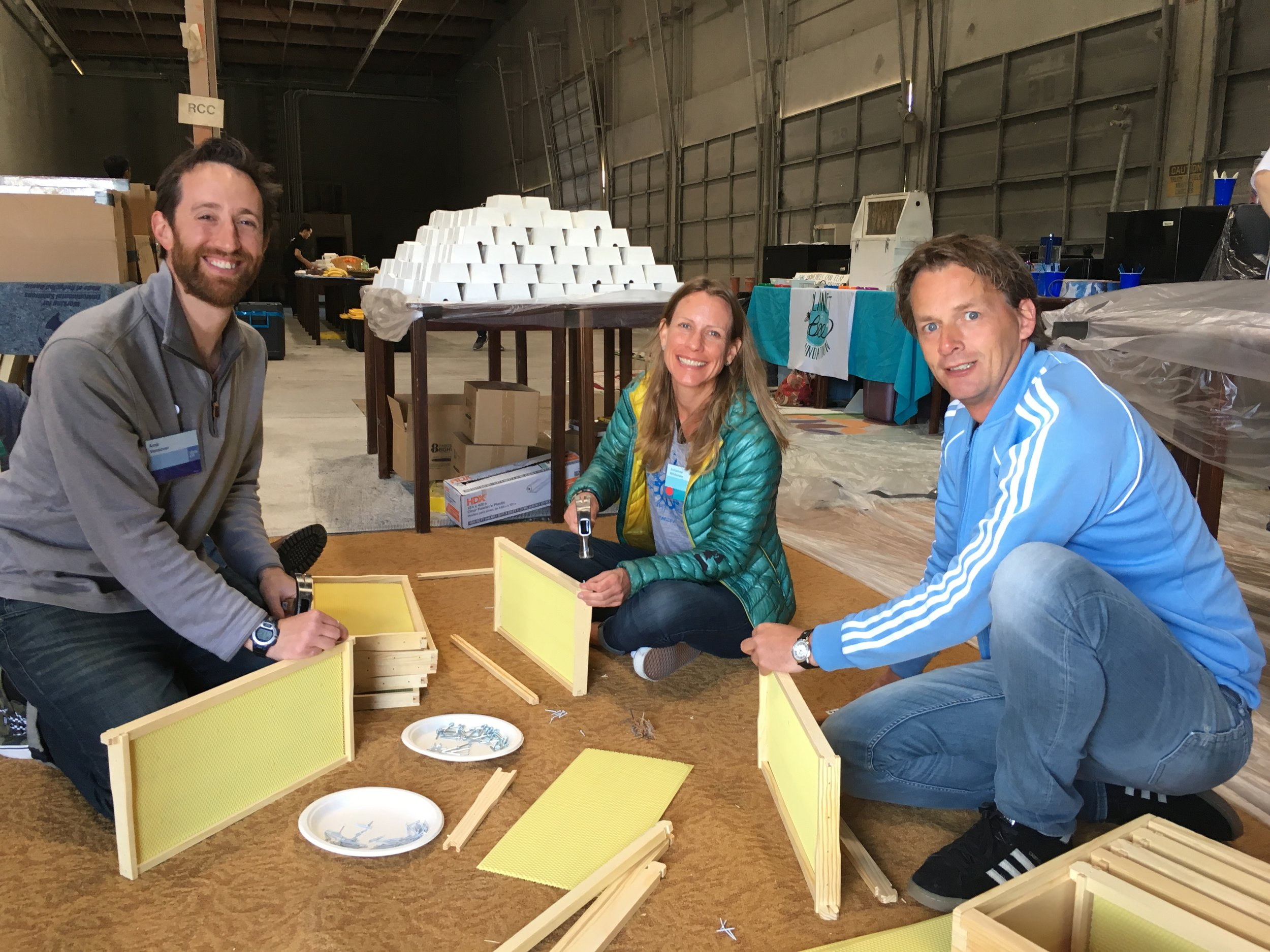 Participants at a beehive building workshop team up to put together frames for a beehive.