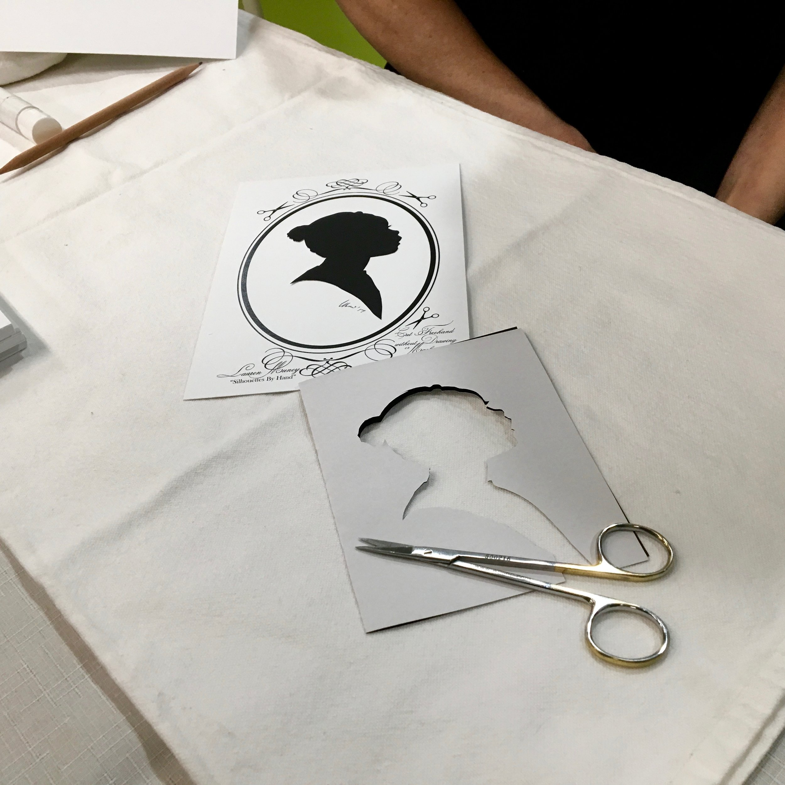 Traditional Silhouette portraits are cut freehand with only scissors, without any device or even a shadow. Experience this rare and old portrait form for yourself. (Photo by Tony Ventouris for Montgomery Parks, USA.  More photos are here. )