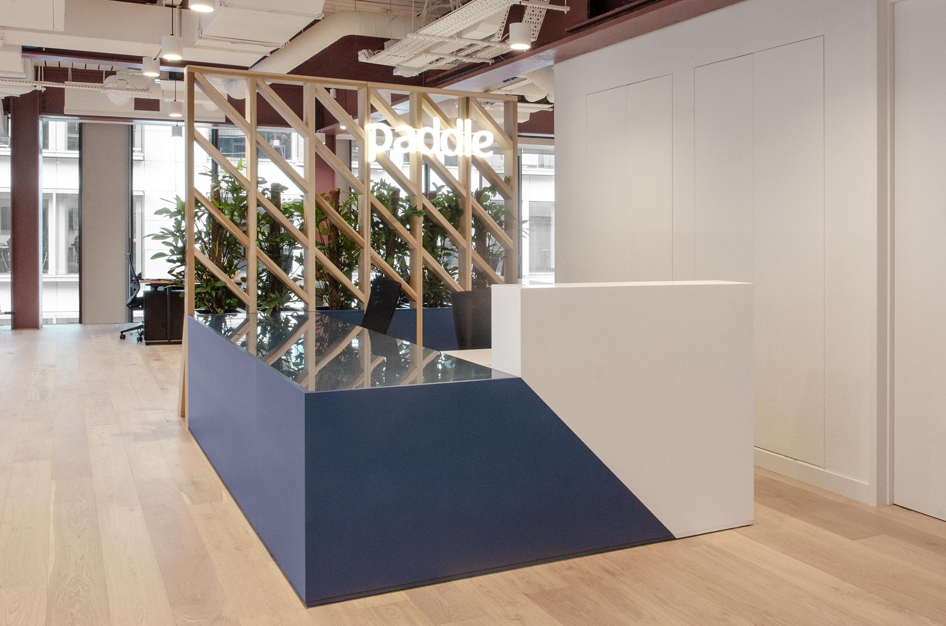 The bespoke Corian desk incorporates illuminated signage and planting