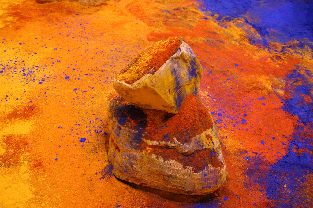 Detail of the red chili powder, turmeric and blue pigment ( nee) on theceramic boulder