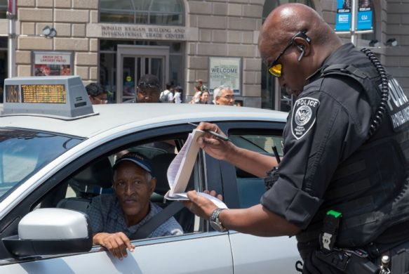 A police officer issues a ticket to a taxi driver in Washington, D.C.