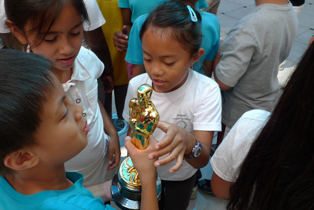 Students from  Strangers No More  holding the Oscar Awarded for the film.