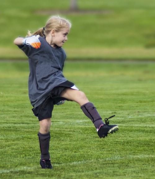 Girl kicking soccer ball as part of MetaSport PlayOn series