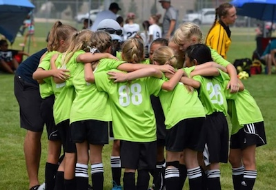 9U-11U MetaSport girls team huddles before kickoff.