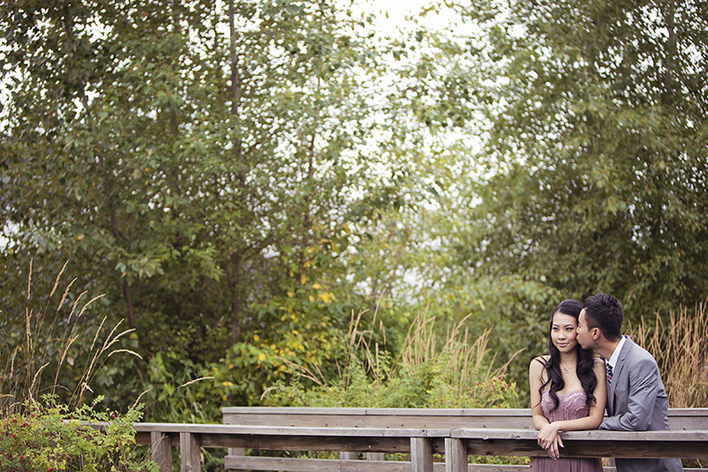 couple leaning on old wooden railing