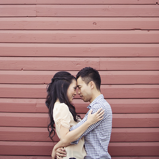couple with heads together in front of red wall