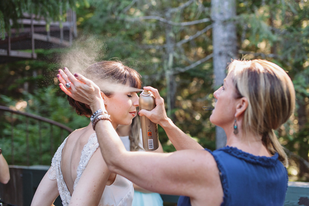 Vancouver Wedding Photo: Hair-stylist spraying a bride with hairspray