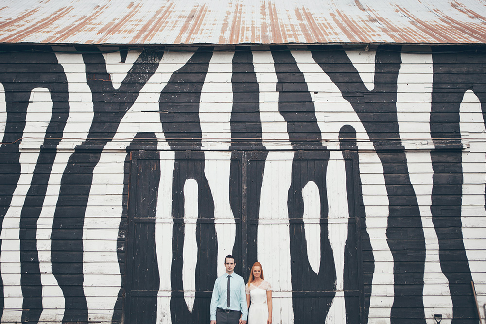 portrait of couple in front of a zebra painted wall  by Vancouver photographer