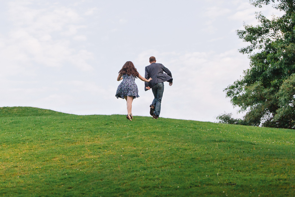Vancouver portrait photography: couple racing up a grassy hill