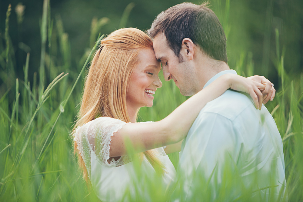 couple with heads together in long grass  by Vancouver photographer