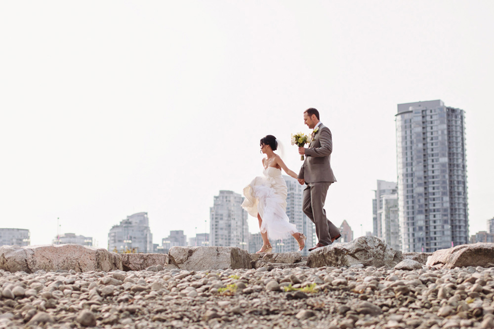 Married couple walking on rocks by Vancouver portrait photographer