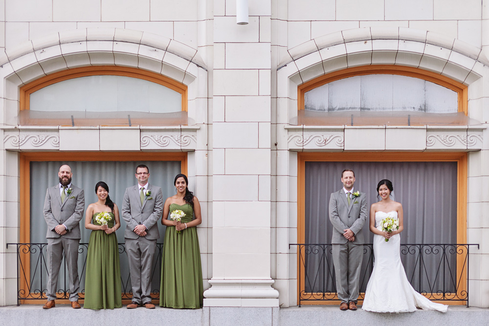 bridal party in front of detailed building and windows