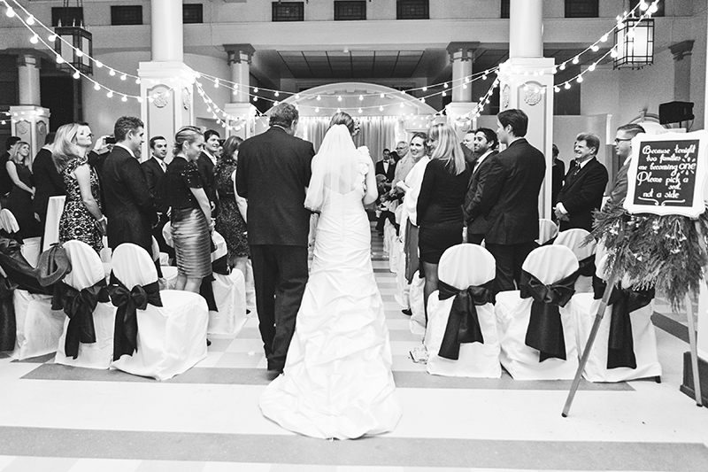 bride walking down aisle with dad from behind
